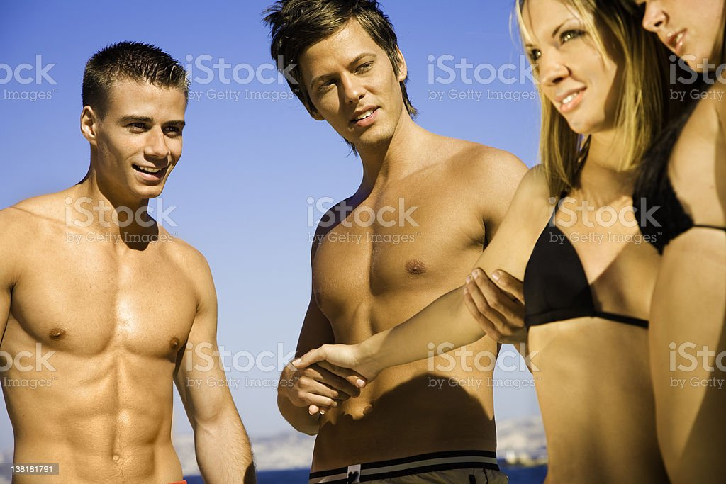 Boys dating girls at the beach royalty-free stock photo