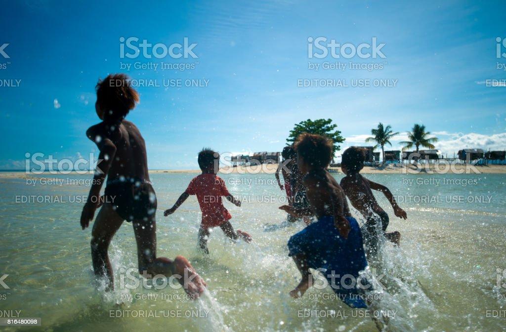 Boys diving into clear blue sea, Semporna, Malaysia stock photo