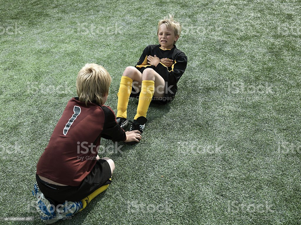Boys (9-10 years) doing sit ups on soccer field, elevated view royalty-free stock photo