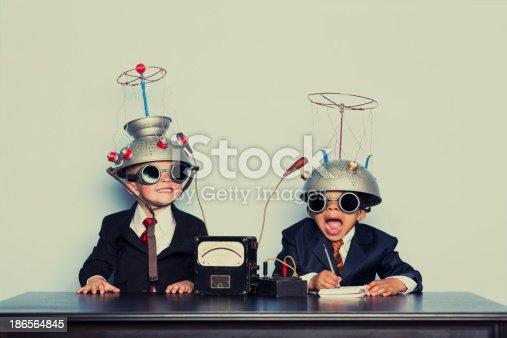 istock Boys Dressed as Businessmen Wearing Mind Reading Helmets 186564845