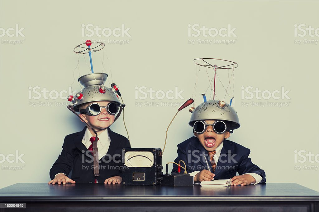 Boys Dressed as Businessmen Wearing Mind Reading Helmets bildbanksfoto