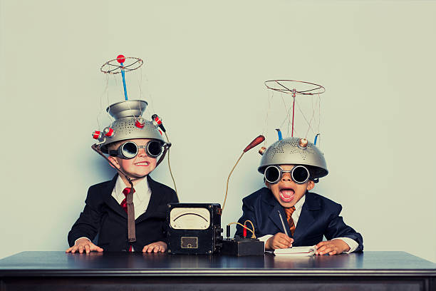 Boys Dressed as Businessmen Wearing Mind Reading Helmets stock photo
