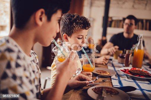 istock Boys drinking fresh orange juice during breakfast with family 983371606