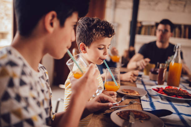 boys drinking fresh orange juice during breakfast with family - drinking juice stock photos and pictures