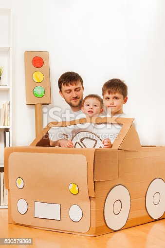496487362 istock photo Boys driving dad in toy car made of cardboard box 530579368