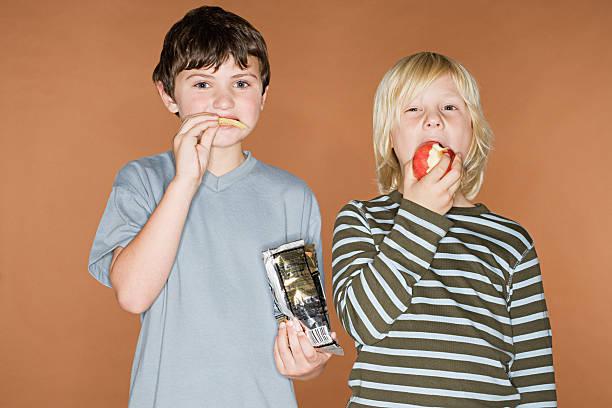jungen essen chips und einem apple - kinder verpackung stock-fotos und bilder