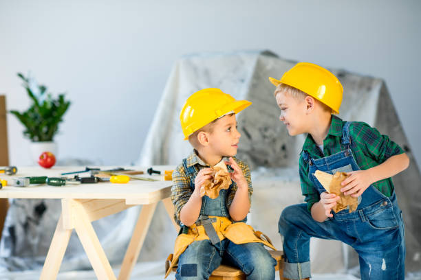 Boys eating sandwiches Two cute boys in helmets holding sandwiches and looking at each other bib overalls boy stock pictures, royalty-free photos & images