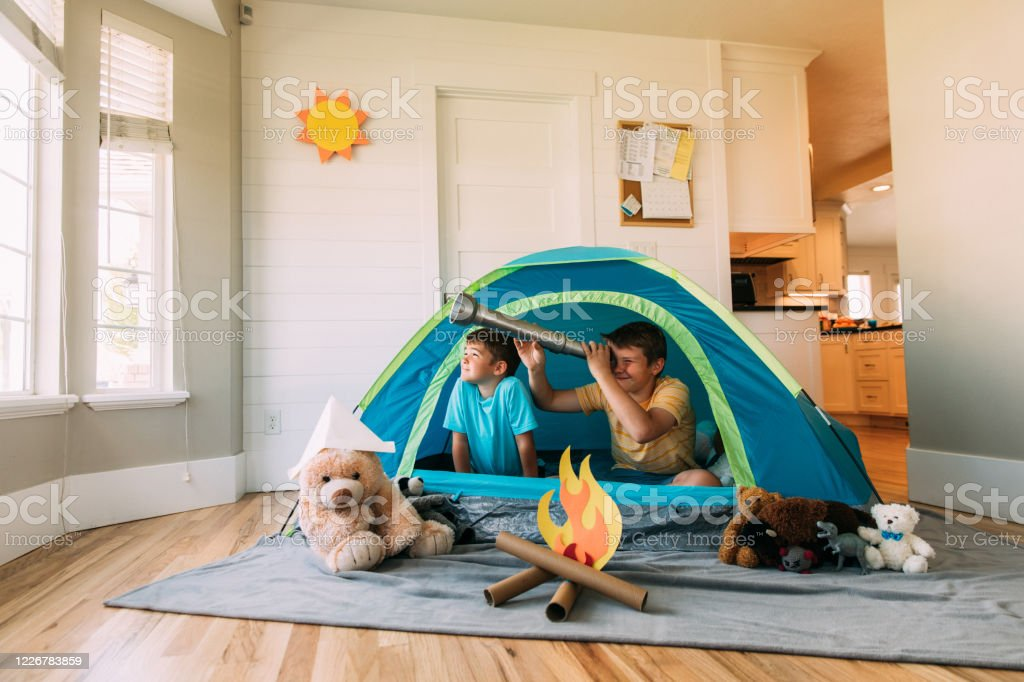 Boys Exploring with Telescope Indoors Two brothers camp inside their home due to the coronavirus restrictions and quarantine. They have pitched a tent along with their stuffed animal friends and have a fake campfire next to their tent. They are searching the skies for stars and dreams. 10-11 Years Stock Photo