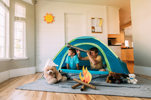 Boys Exploring With Telescope Indoors Stock Photo - Download Image Now