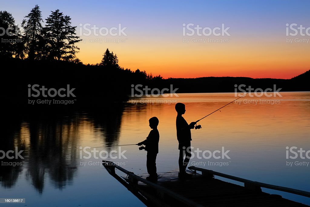 Boys Fishing at Sunset stock photo