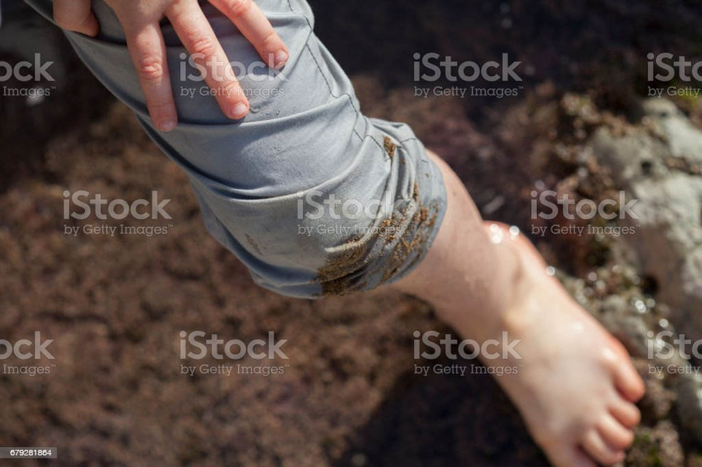 Boy's Foot and Leg Wet While Playing Near Tidal Pools Faded Tones stock photo