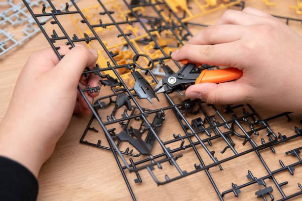 A boy's hand assembling plastic models using tools. stock photo