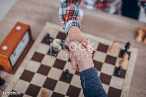 Two young boys, playing chess in school of chess,  handshake after a chess game.