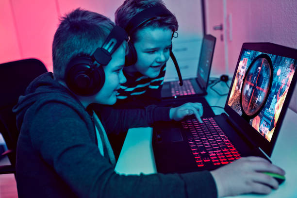 boys help each other while playing esports game on laptops at night - esports stock photos and pictures