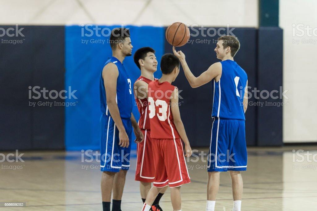 Boys high school basketball practice - four players goofing around...