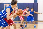 Boys high school basketball team: player about to shoot over defender