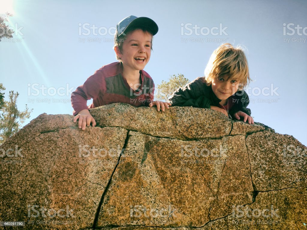 Boys hiking and playing in the mountains stock photo