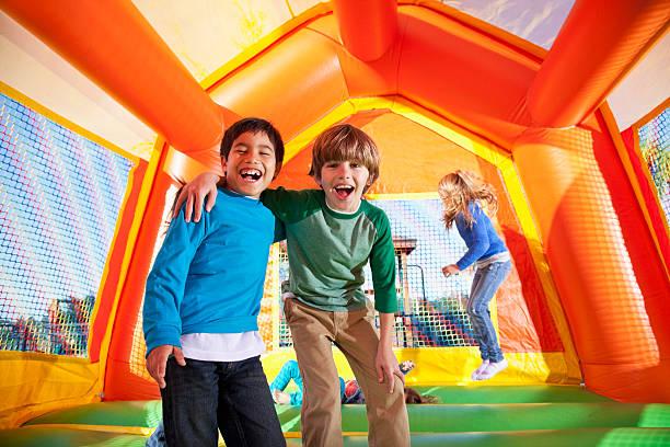 jungen in bounce house - kinderparty spiele stock-fotos und bilder
