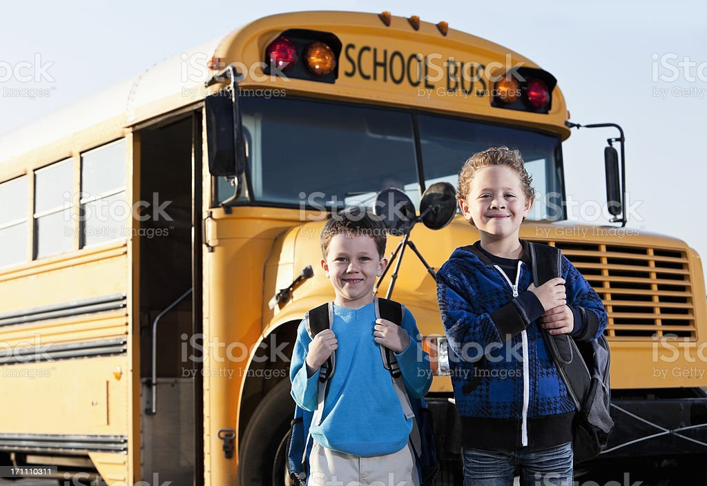 Boys in front of school bus stock photo