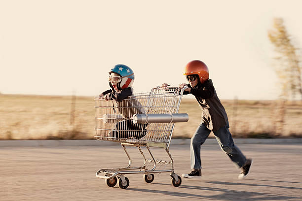 boys in helmets race a shopping cart - daredevil stock pictures, royalty-free photos & images
