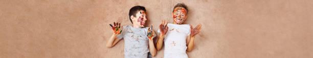 Jungs in Farben am Boden liegend – Foto