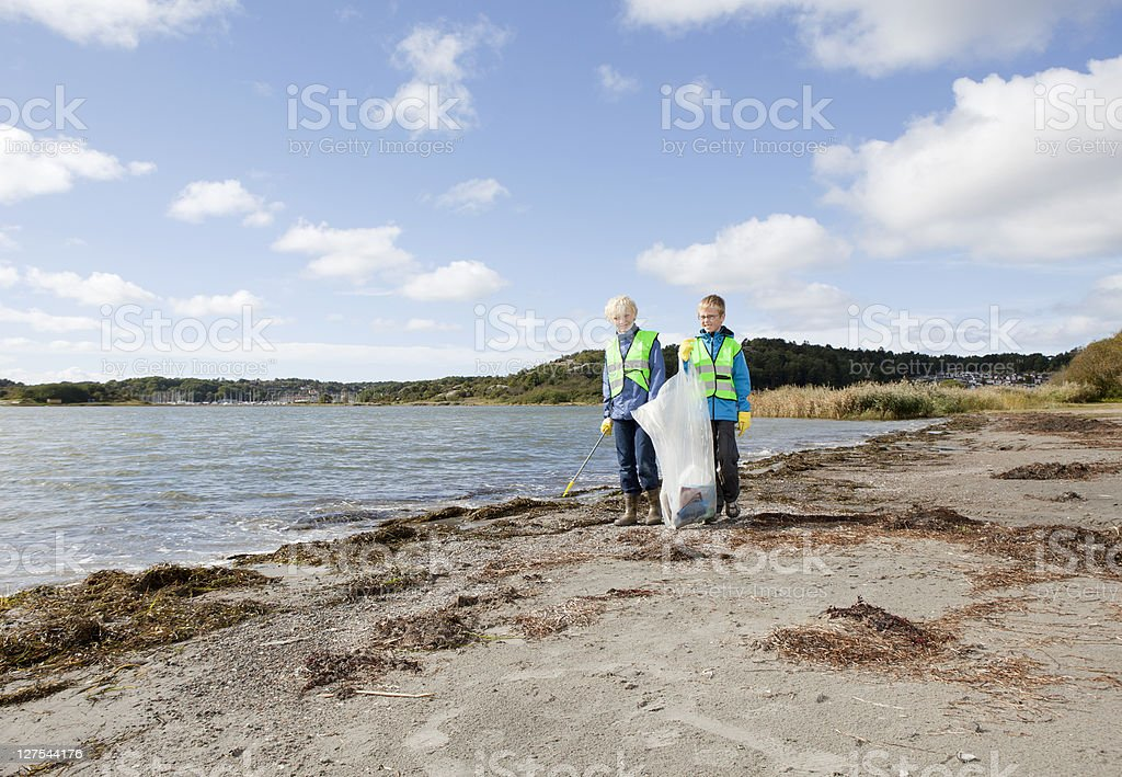 Boys in safety vests cleaning beach stock photo