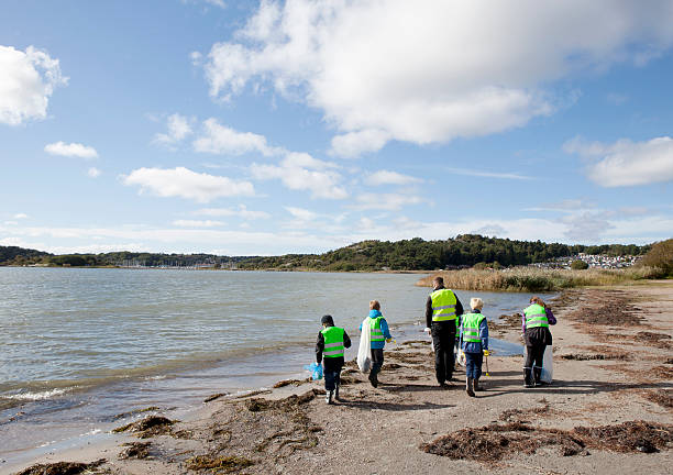 Boys in safety vests cleaning beach  environmental cleanup stock pictures, royalty-free photos & images