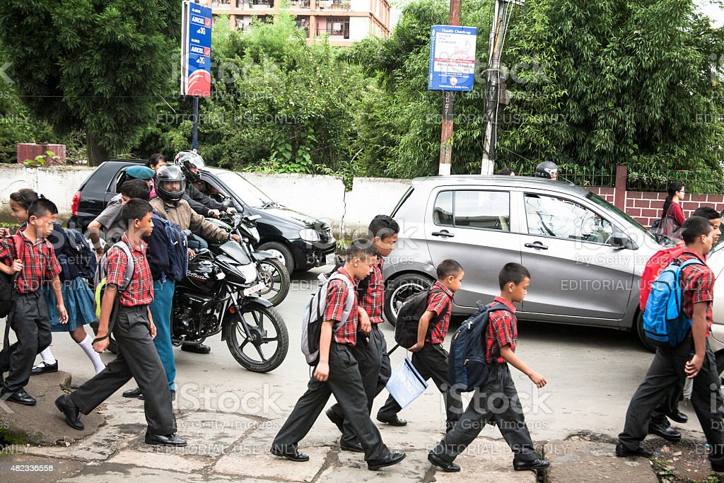 Boys in Shillong, India walking to school down busy street. stock photo