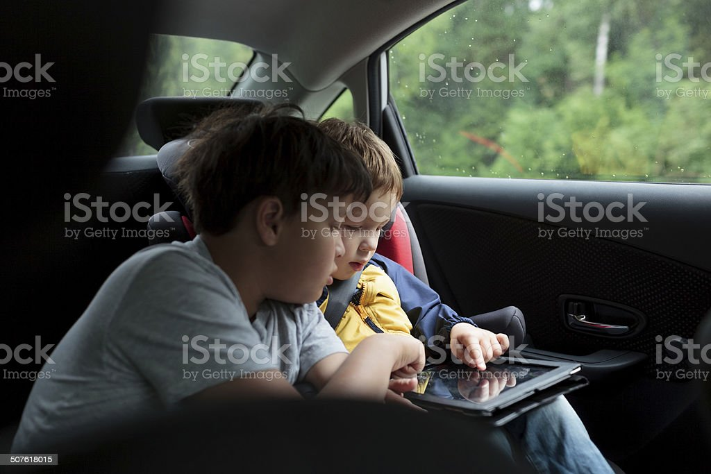 Boys in the car using a touchpad stock photo