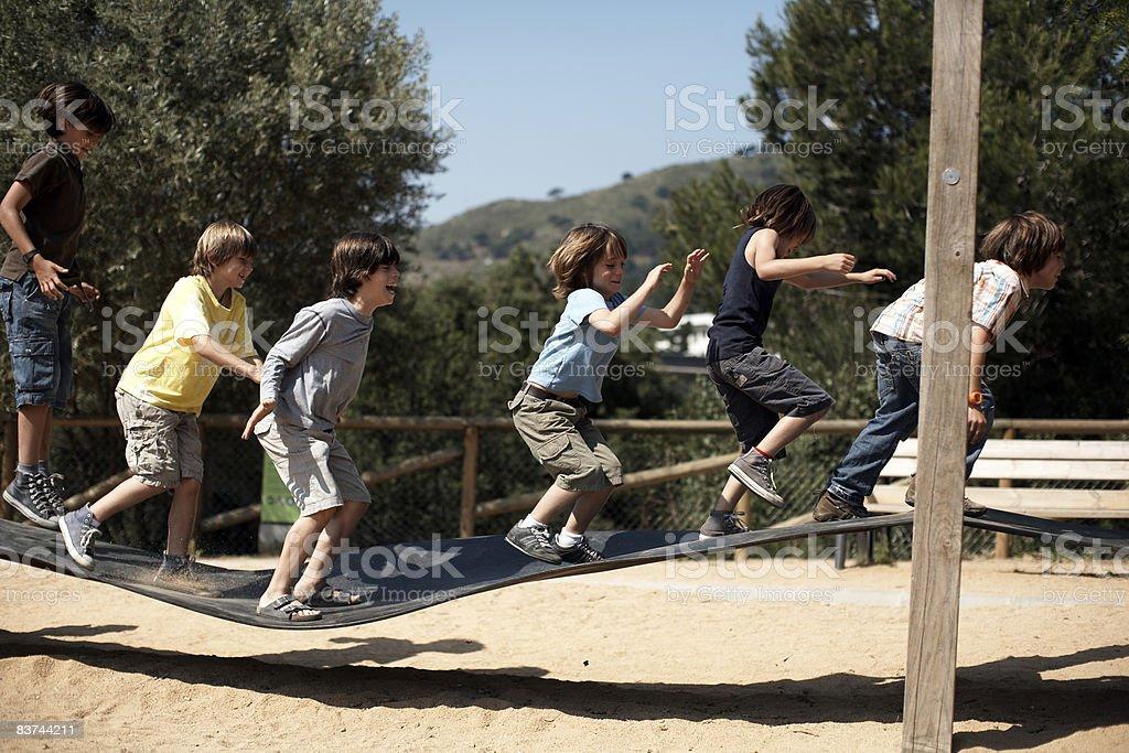 Ragazzo saltare sul parco giochi struttura foto stock royalty-free