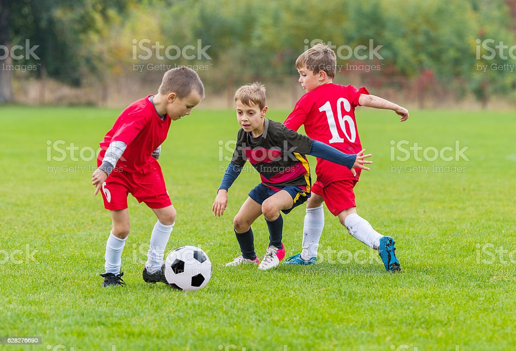 Boys kicking ball stock photo