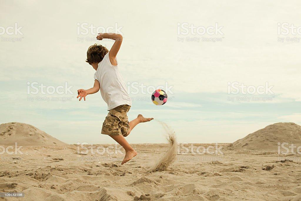 Garçons coup de pied de football sur la plage - Photo