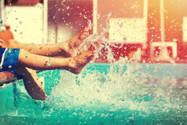 Piernas de los chicos salpicaduras de agua en época de piscina - foto de stock