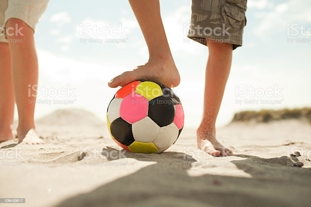 Ragazzo con il pallone da calcio sulla spiaggia - foto stock