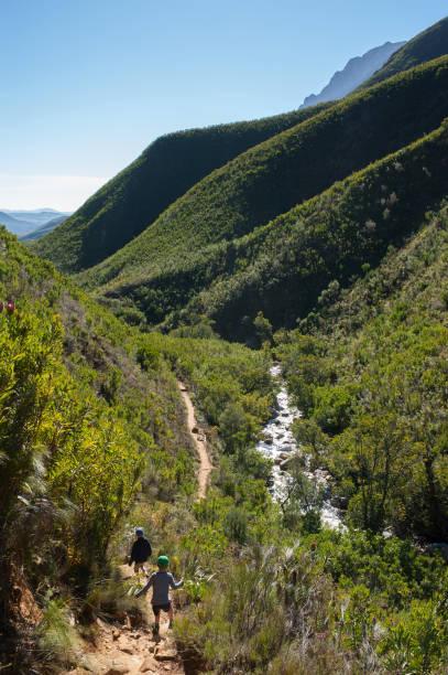 Boys on mountain path hiking stock photo