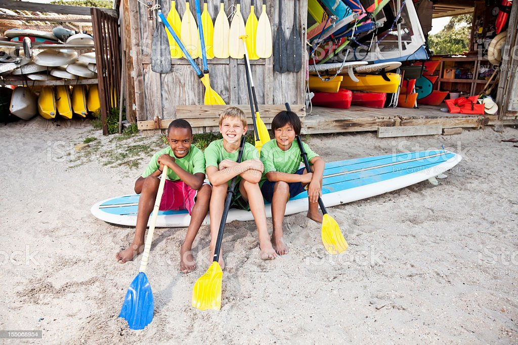 Boys on paddle board by water sports equipment shack stock photo
