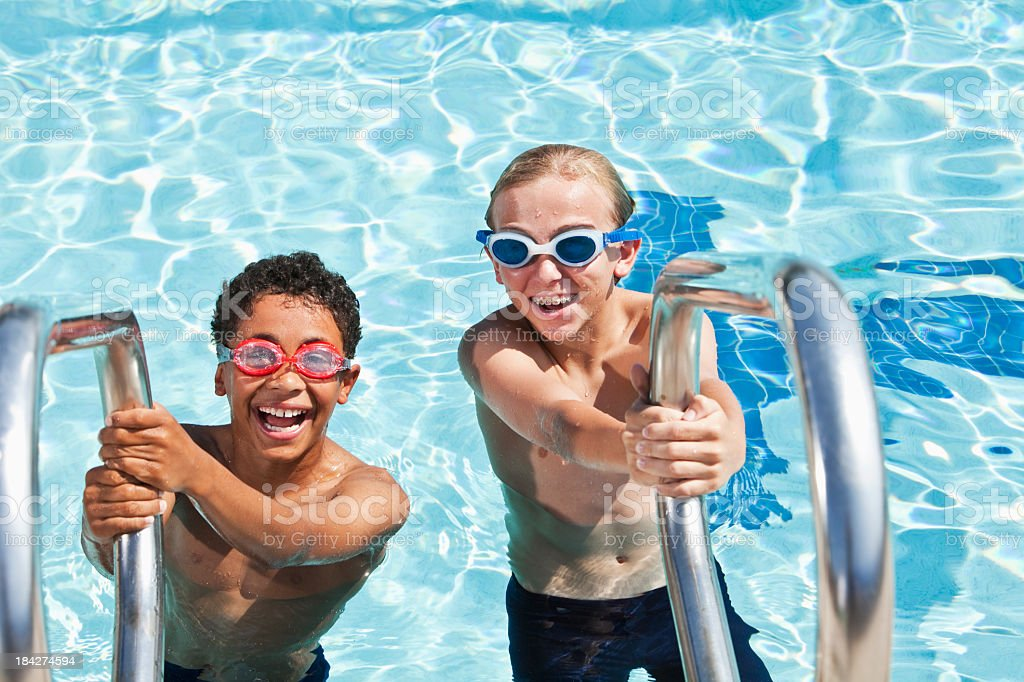 Boys on swimming pool ladder stock photo