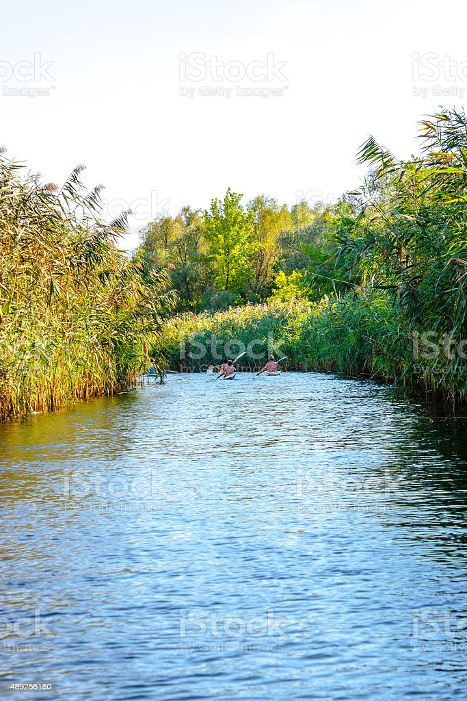 boys paddle canoes on the river stock photo