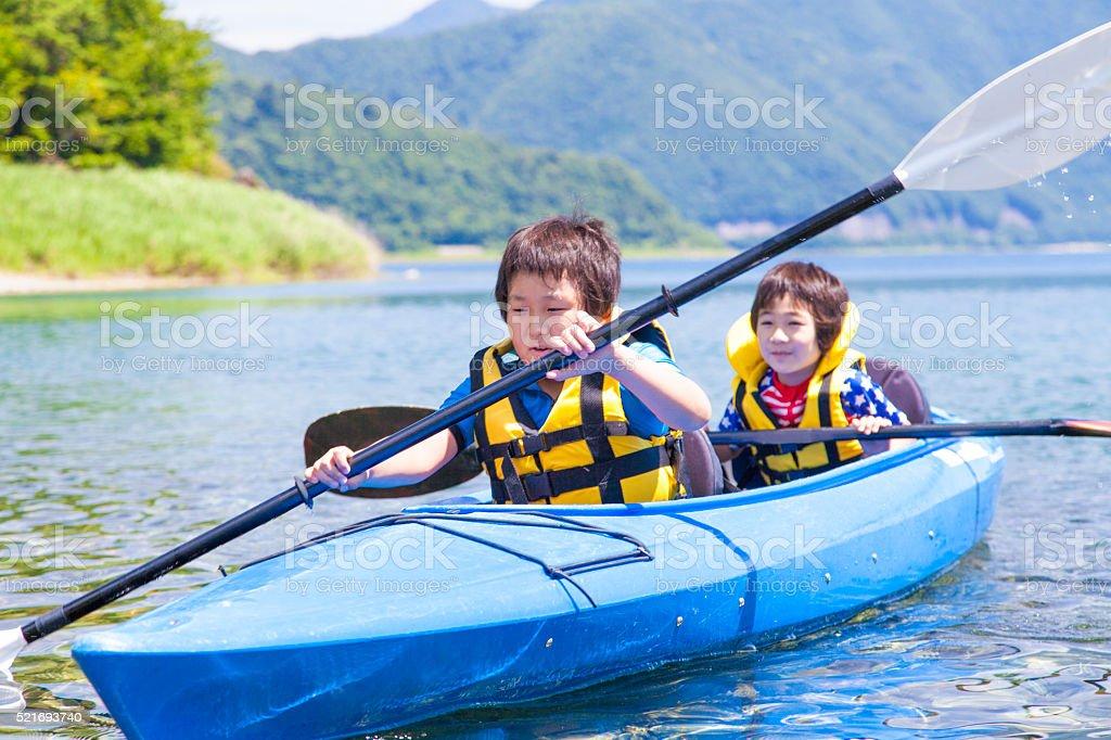 Boys paddling on the tandem kayak stock photo
