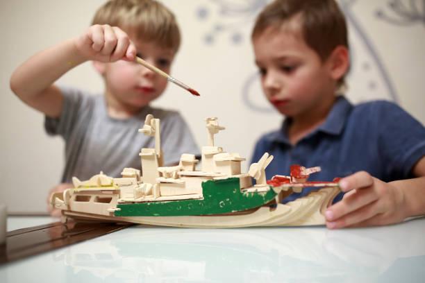 jungen malerei holzmodell des kriegsschiffes - kindergarten workshop stock-fotos und bilder