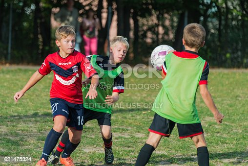 621475196 istock photo Boys play football on the sports field 621475324