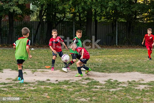 621475196 istock photo Boys play football on the sports field 621500098