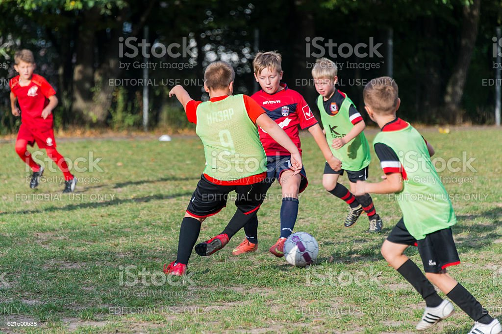 Boys play football on the sports field photo libre de droits