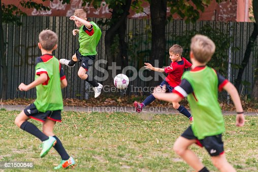 621475196 istock photo boys play football on the sports field 621500846