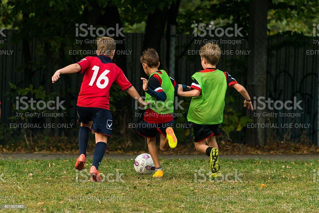 Boys play football on the sports field photo libre de droits