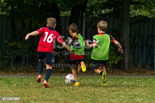 621475196 istock photo Boys play football on the sports field 621501382
