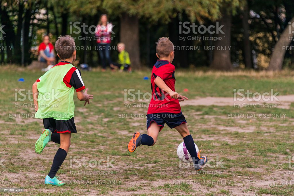 Boys play football on the sports field foto stock royalty-free