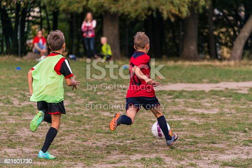 621475196 istock photo Boys play football on the sports field 621501730