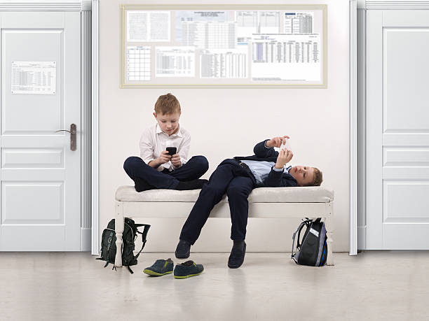 Boys play phones in a public institution Boys play phones in a public institution - a school or clinic absentee stock pictures, royalty-free photos & images