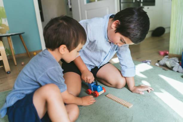 pojkar spelar med trä tåg - working from home bildbanksfoton och bilder